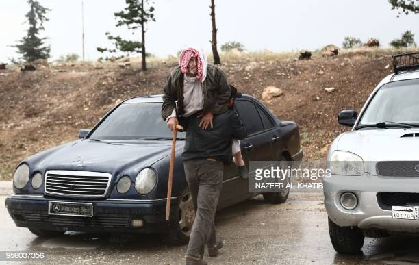 A Syrian carries an elderly man upon arriving in a convoy at Abu alZandin checkpoint near alBab in northern Syria on May 8 after being evacuated from...