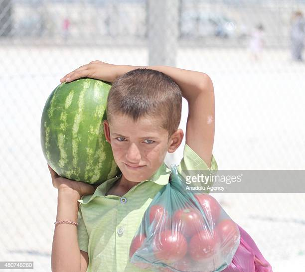 Syrian child carries a watermelon at a refugee camp in Suruc district of Sanliurfa on July 14 as the Syrian Kurds who fled the clashes between Daesh...