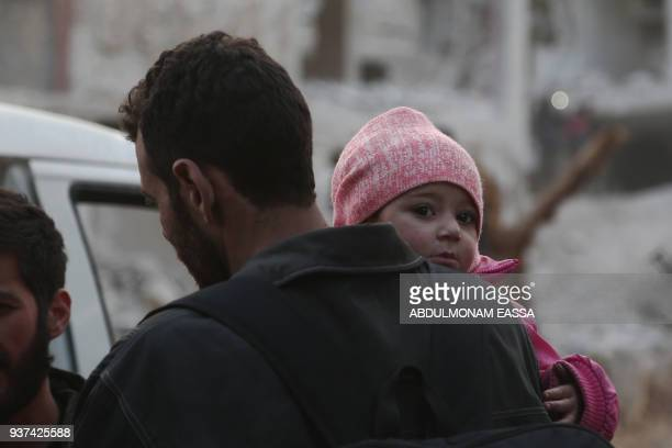 A Syrian child clings on to her father as they prepare to evacuate one of the few remaining rebelheld pockets in Arbin in Eastern Ghouta on the...