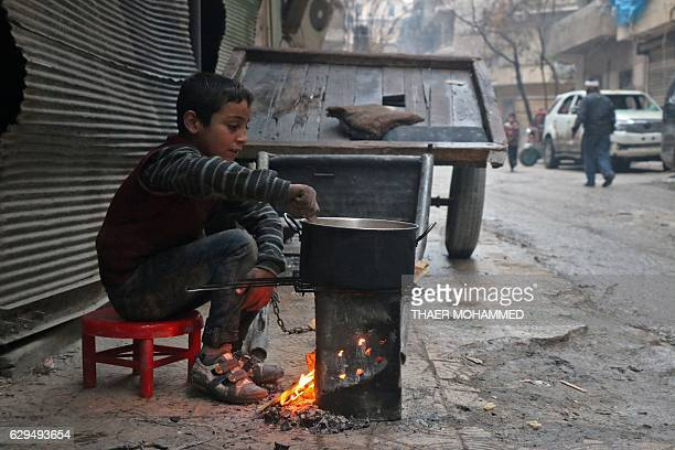 A Syrian child cooks in the street in a rebelheld area of Aleppo on December 13 during an operation by Syrian government forces to retake the...