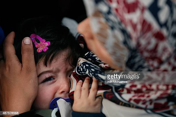 Syrian child cries as her mother holds her in a surging crowd as the girl's family tries to board a train leaving for the Austrian border at the...