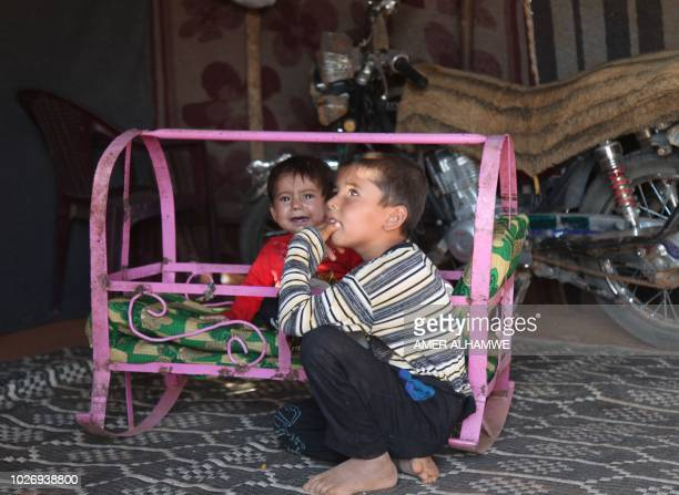 A Syrian child crouches next to another sitting in a metal crib outside a tent at a camp for displaced civilians fleeing from advancing Syrian...