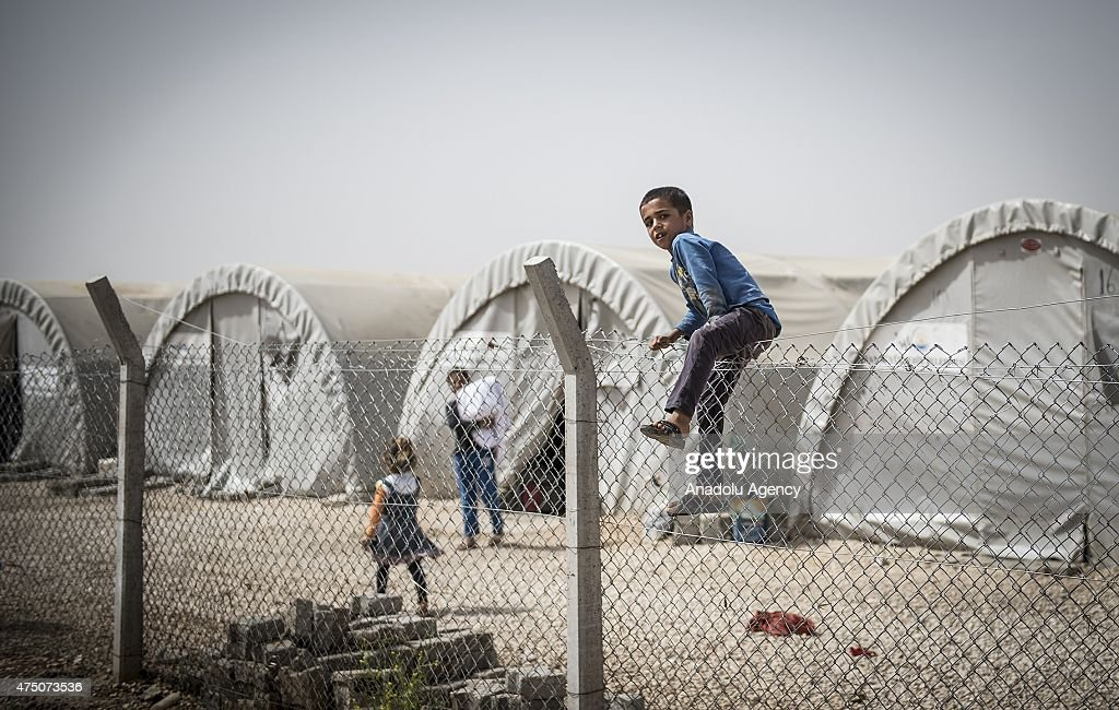 A Syrian child enjoys behind wire nettings in Suruc district of Sanliurfa, Turkey on May 28, 2015. Syrian refugees fled their home due to the civil war live under harsh conditions in tents.