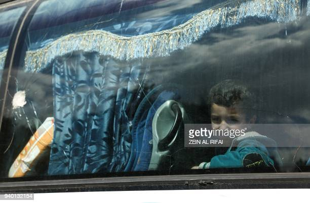A Syrian child evacuated form Eastern Ghouta looks out from the window of a bus after arriving in Qalaat alMadiq some 45 kilometres northwest of the...