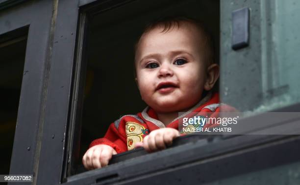 A Syrian child evacuated from a rebelheld area in Syria's central Homs province looks from the window of a bus after arriving in a convoy at Abu...