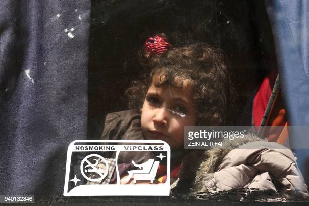 A Syrian child evacuated from Eastern Ghouta looks out from the window of a bus after arriving in Qalaat alMadiq some 45 kilometres northwest of the...