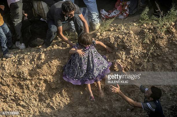 A Syrian child fleeing the war is helped as she enters Turkish territory illegally near the Turkish border crossing at Akcakale in Sanliurfa province...