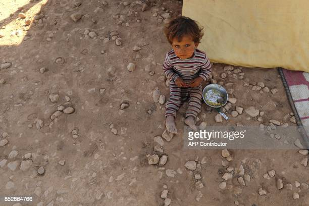 Syrian child from the eastern city of Deir Ezzor, who was displaced by the war against the Islamic State group, sits next to a rug outside the Ain...