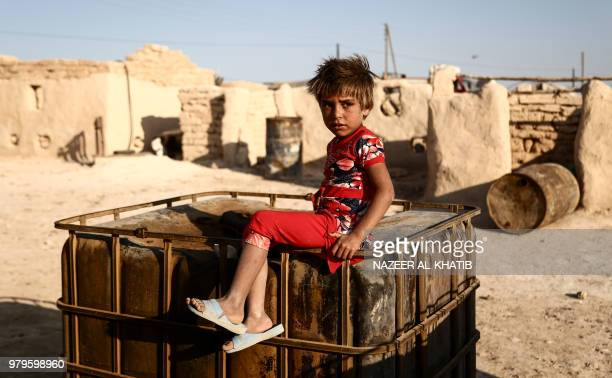 Syrian child from the northern city of Manbij displaced by fighting between the Syrian Democratic Forces and Islamic State group fighters sits...