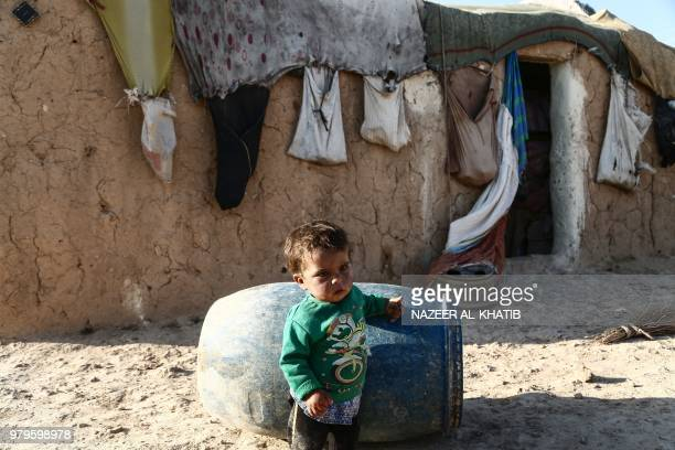 Syrian child from the northern city of Manbij displaced by fighting between the Syrian Democratic Forces and Islamic State group fighters stands next...