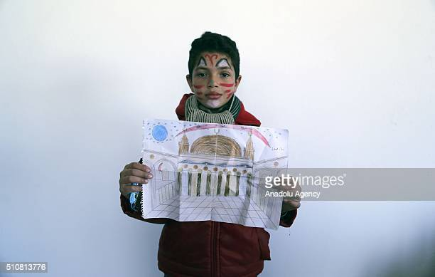 Syrian child Hasan Dater who escaped from Civil war in Syria holds her painting as she continues her education in Furkan primary school at Reyhanli...