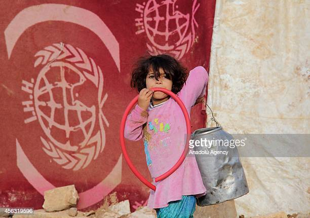 Syrian child holds a bucket at the tent city close to Al Salama border gate in Azez district of Aleppo, Syria on September 29, 2014.