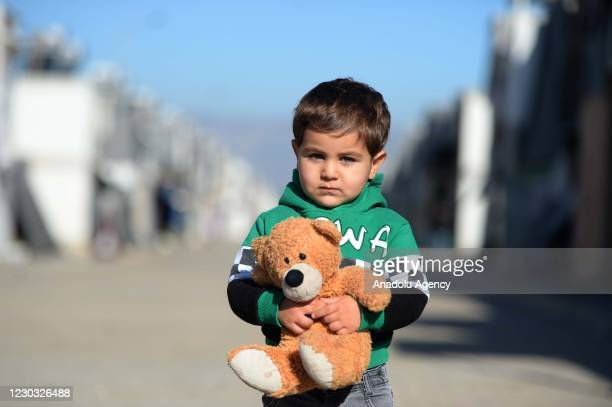 Syrian child holds a teddy bear at a temporary refuge center in Turkey's Kahramanmaras, on December 25, 2020. Syrians who fled the civil war in Syria...