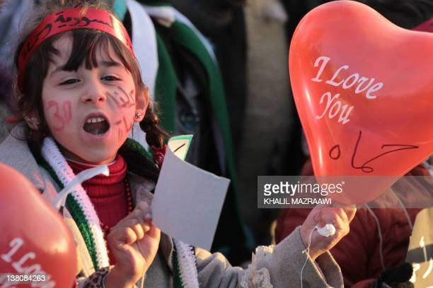 A Syrian child living in Jordan chants slogans holding a baloon with a message in English and Arabic that reads I love you Hama during a...
