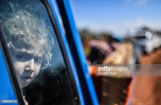 A Syrian child looks on ahead of crossing to the Turkishbacked Syrian rebels side at a check point in the village of Anab on March 17 as civilians...