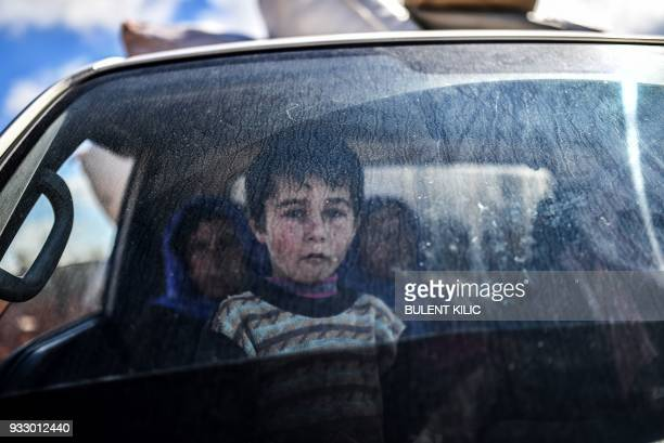 Syrian child looks on as people arrive at a check point in the village of Anab ahead of crossing to the Turkishbacked Syrian rebels side on March 17...