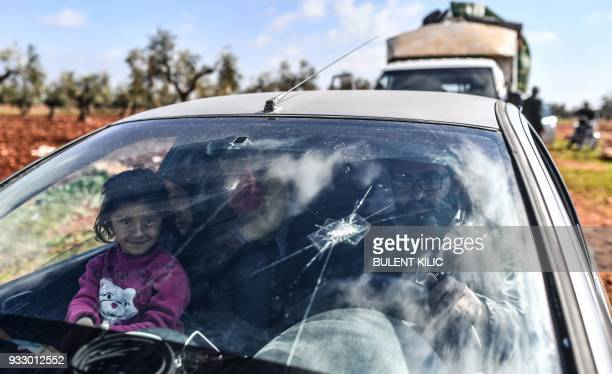 A Syrian child looks on as people arrive at a check point in the village of Anab ahead of crossing to the Turkishbacked Syrian rebels side on March...