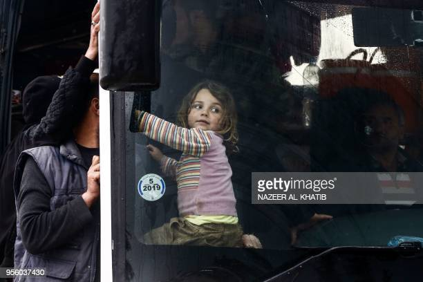 A Syrian child looks through the windshield of a bus while sitting upon arriving in a convoy at Abu alZandin checkpoint near alBab in northern Syria...