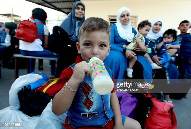 Syrian child Luay son of Rawad Kurdi drinks milk before boarding a bus with his family on September 17 2018 as they return to Syria after living as...