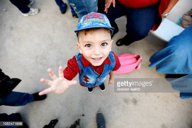 Syrian child Luay son of Rawad Kurdi smiles before boarding a bus with his family on September 17 2018 as they return to Syria after living as...