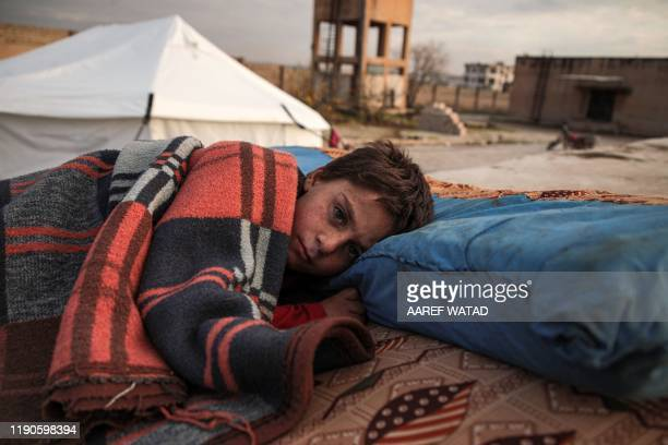 Syrian child, one of those who fled from government forces' advance on Maaret al-Numan in the south of Idlib prvoince, sleeps on a futon in the open...