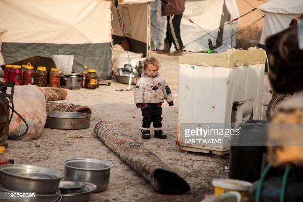 Syrian child, one of those who fled from government forces' advance on Maaret al-Numan in the south of Idlib prvoince, walks by a rolled-up carpet...