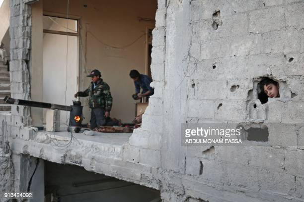 Syrian child peaks from a hole in the wall as a youth makes tea in the rebel-held besieged town of Arbin, in the eastern Ghouta region on the...