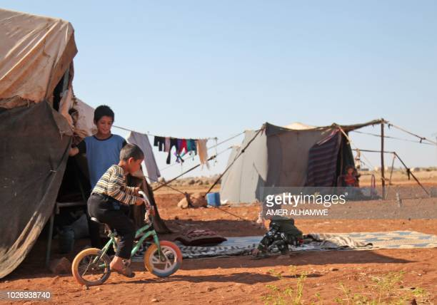A Syrian child rides a bicycle outside a tent at a camp for displaced civilians fleeing from advancing Syrian government forces close to a Turkish...
