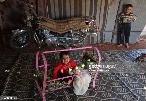 A Syrian child sits in a metal crib outside a tent at a camp for displaced civilians fleeing from advancing Syrian government forces close to a...