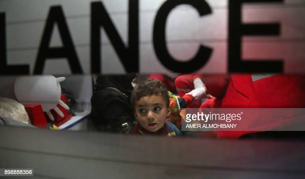 A Syrian child sits in an ambulance during an evacuation operation by the International Committee of the Red Cross in Douma in the eastern Ghouta...