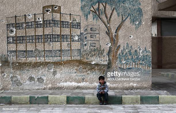 Syrian child sits in front of a mural covered in bullet holes on the wall of a former school in the rebelheld region of Eastern Ghouta on the...