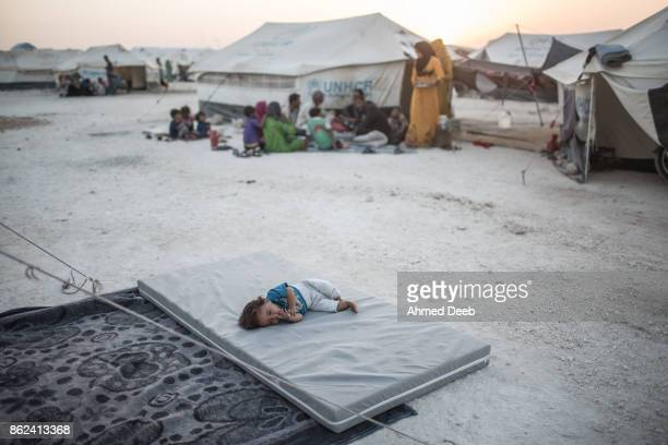 Syrian child sleeps in front of a tent at a makeshift camp in Ain Issa, 50 kilometers north of Raqqa city on August 2, 2017. The Battle of Raqqa was...