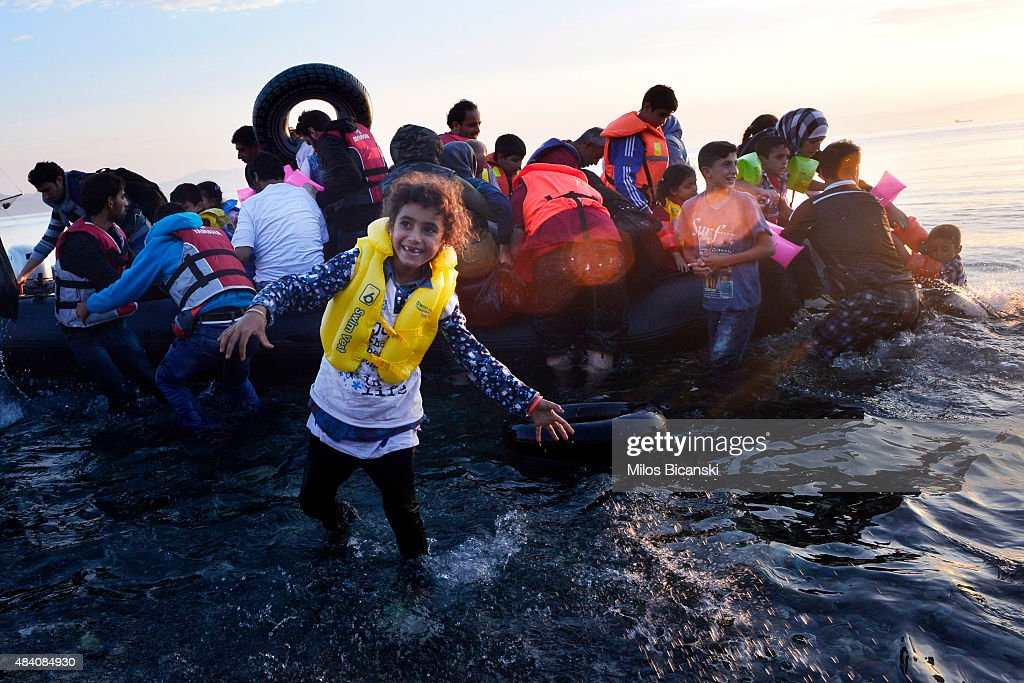 A Syrian child smiles as refugees arrive at a beach on the Greek island of Kos after crossing a part of the Aegean sea from Turkey to Greece in a dinghy on August 15, 2015 in Kos, Greece. The Greek government has sent a cruise ship to the island of Kos which will be able to house up to 2,500 refugees and operate as a registration centre, after 2,000 Syrian refugees were locked in an old stadium during a registration process and left without water for more than a day.