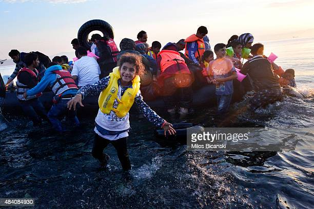 Syrian child smiles as refugees arrive at a beach on the Greek island of Kos after crossing a part of the Aegean sea from Turkey to Greece in a...