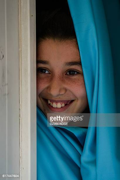 A Syrian child smiles at a refugee camp in the Kilis district of Gaziantep southeastern Turkey on October 23 2016 France's foreign minister urged the...