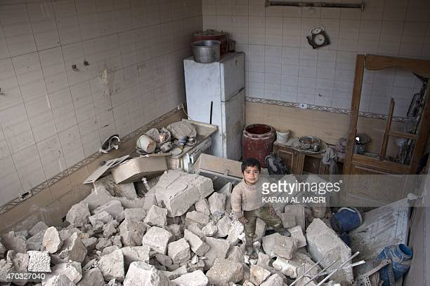 A Syrian child stands amid rubble after his family's building partially collapsed following a reported airstrike by government forces on a rebel held...
