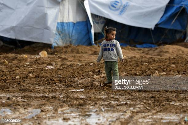 A Syrian child stands out in the open in Abu AlKhashab camp for the displaced from the eastern province of Deir Ezzor northwest of the city of Deir...