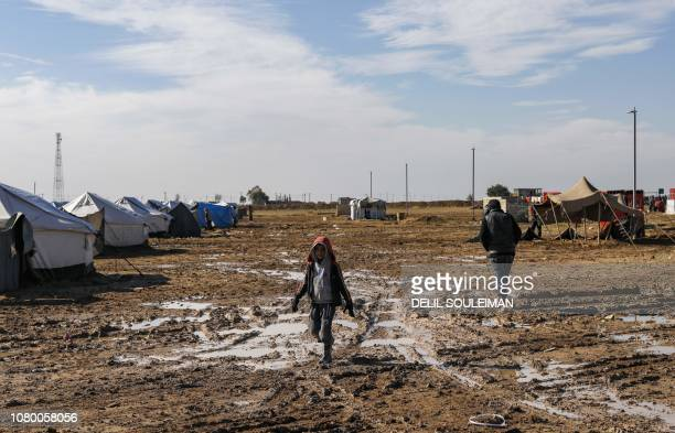 A Syrian child walks in the mud in Abu AlKhashab camp for the displaced from the eastern province of Deir Ezzor northwest of the city of Deir Ezzor...