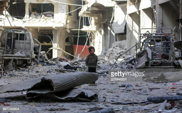 Syrian child walks past debris down a street with damaged buildings on the edges of Zamalka in Eastern Ghouta on the outskirts of the Syrian capital...