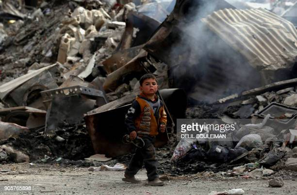 A Syrian child walks past the debris of destroyed buildings in the northern Syrian city of Raqa on January 11 2018 after a huge military operation...