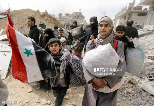 Syrian child walks with a national flag with other civilians evacuated from the Eastern Ghouta enclave, as they pass with belongings through the...