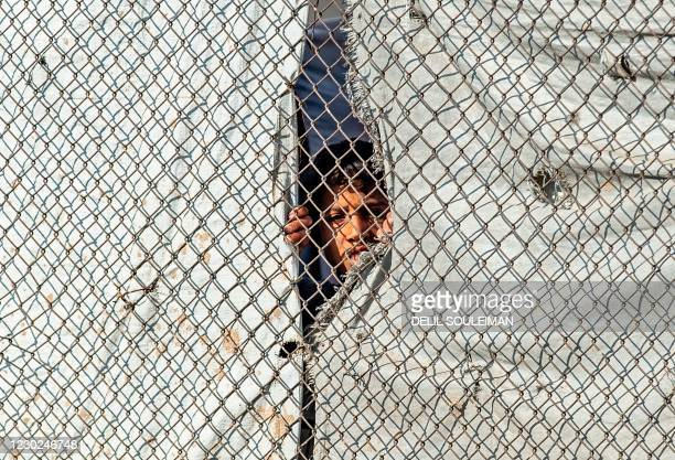 Syrian child watches displaced Syrians, suspected of being related to Islamic State group fighters, as the board a bus at the Kurdish-run al-Hol...
