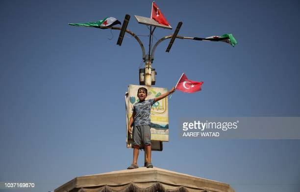 A Syrian child waves a Turkish flag as he stands on a shade above other protesters during a demonstration against the Syrian government in the...
