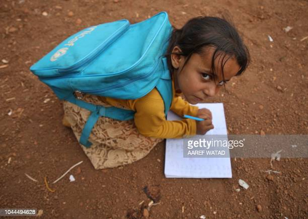 A Syrian child who fled with her family from the northern countryside of Hama writes in a notebook in the yard of the makeshift school of 'Zuhur...