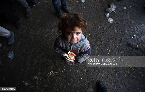 Syrian child who fled with his family from rebelheld areas in the city of Aleppo reacts as he holds a sandwich on December 1 at a shelter in the...