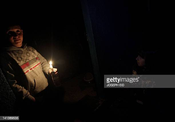 A Syrian child who fled with his family the violence in the flashpoint city of Homs holds a candle in a room during a power outage at a school which...