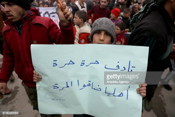 Syrian child who used to live in Tadef holds a placard during a protest demanding Assad Regime forces to leave Tadef in Al Bab district which was...