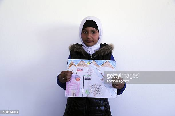 Syrian child Yeter Hussain who escaped from Civil war in Syria holds her painting as she continues her education in Furkan primary school at Reyhanli...