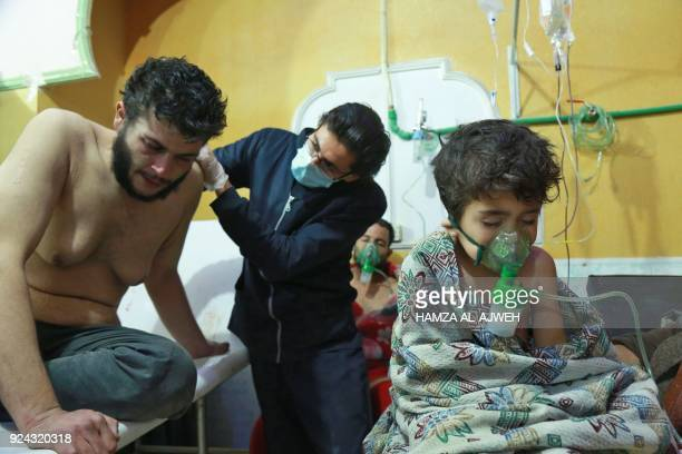 TOPSHOT Syrian children and adults receive treatment for a suspected chemical attack at a makeshift clinic on the rebelheld village of alShifuniyah...