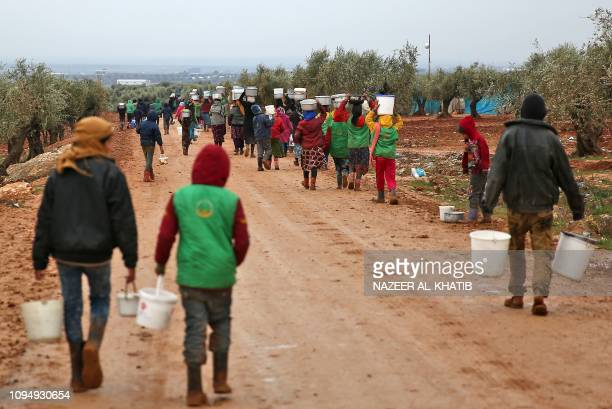 Syrian children and women carry pots of food distributed by a humanitarian aid workers at a makeshift camp for displaced people near the village of...